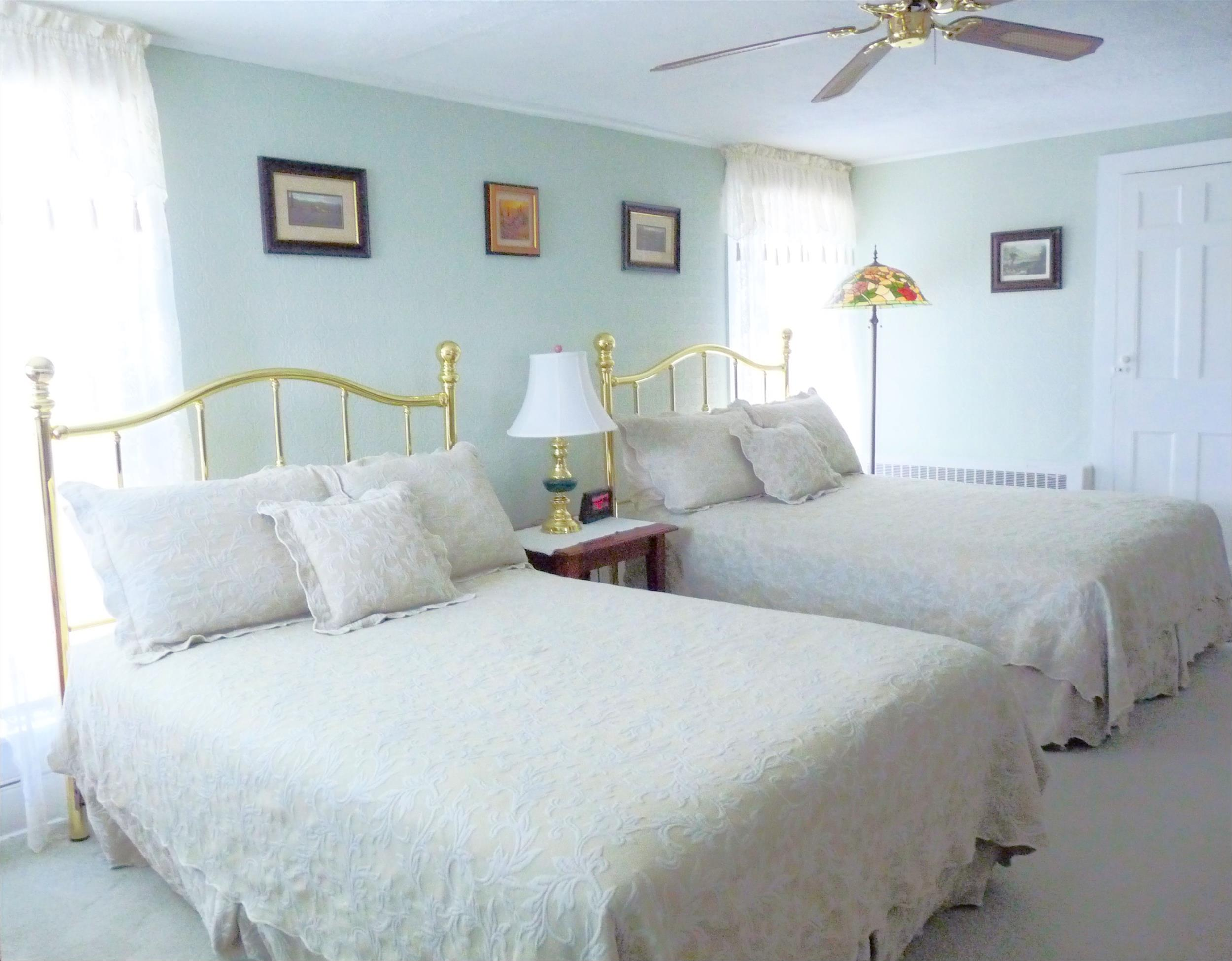 two beds with white bed spreas